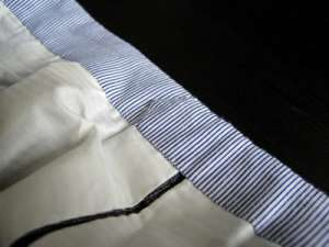 Gray pants with a waistband curtained with striped blue fabric