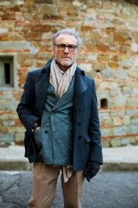 This man does works wtihin simple color schemes of grey and beige. Ultimately, he is just sticking to dull-colored monochromatic items. But it works so well because in shifting emphasis away from color, he emphasizes fit of the jacket and the pronounced length of the scarf.